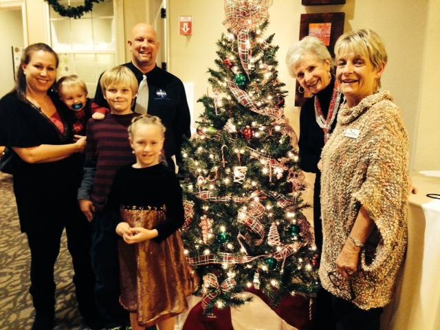 Daniel Doré and family, Betty Schleder with Honor Flight Austin, and me, Virginia Lazenby, around my Christmas Memories tree.