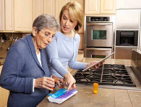 Elderly Woman Organizing Medicine in Pill Box with  Caregiver's